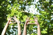People show heart of hands on natural background
