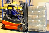 Worker And Forklift Loader At Warehouse