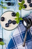 Top View Over Blueberries With Yogurt On Rustic Table