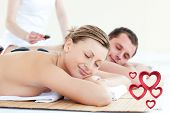 Young couple having a massage with hot stone against pink hearts