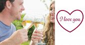 Cheerful couple toasting with white wine against valentines love hearts
