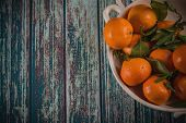 Freshly Picked Clementines In Rustic Bowl On Blue Table