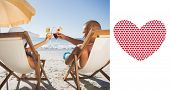 Happy couple clinking their glasses while relaxing on their deck chairs against valentines day pattern