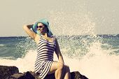 Beautiful woman sitting on a stone and splashing in the sea. Vintage style