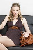 portrait of woman with a handbag sitting on sofa