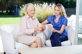 Care aid playing card game with senior woman in retirement home.