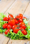 foto of plum tomato  - Tiny plum tomatoes on salad leaf on table - JPG
