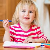 happy three-year-old girl draws felt-tip pens at home