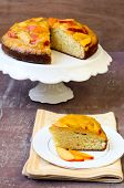 stock photo of peach  - Sponge cake with peach mousse on top and slices of peaches selective focus - JPG