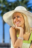 Beautiful blond young woman or girl in her twenties happy smiling wearing sun hat resting on her hand in sunshine on summer day with blue sky and palm trees