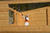 image of air paint gun  - A painter uses an airless spray to apply timber preservative - JPG