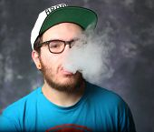 pic of exhale  - Young man in Brooklyn baseball cap exhaling vapor from electronic cigarette - JPG