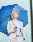 business, bad weather and people and concept - young serious businesswoman with umbrella outdoors