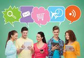 people, communication, school and technology concept - smiling friends with smartphones and tablet pc computers over green board background with text bubbles