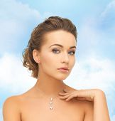 beauty and jewelry concept - woman wearing shiny diamond pendant