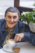 Portrait of disabled man with cerebral palsy sitting at outdoor cafe and drinking coffee.