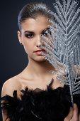 Portrait of young beauty in black boa holding fancy silver fan.