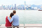 Hong Kong skyline and Victoria harbour. Couple tourists enjoying view and sightseeing on Tsim Sha Tsui Promenade and Avenue of Stars in Victoria harbour, Kowloon, Hong Kong. Tourism travel concept.