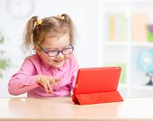 Kid with tablet PC in glasses learning with great interest