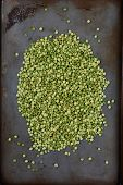 High angle shot of a pile of green split peas on a well used metal baking sheet. Vertical Format.