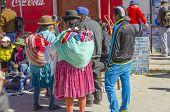 UYUNI, BOLIVIA, MAY 15, 2014:  Local women in traditional attire visit street market