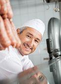 Portrait of confident male butcher smiling in butchery