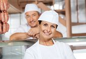 Portrait of happy mature female butcher with male colleague in background at shop