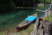 image of rest-in-peace  - A canoe rests tethered to a tree stump on a quiet lake - JPG