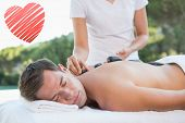 Handsome man getting a hot stone massage poolside against red heart