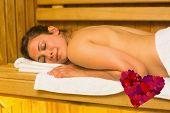 Happy brunette lying down in a sauna against heart