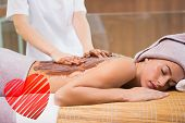 Attractive woman receiving chocolate back mask at spa center against red heart
