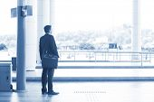 stock photo of indian blue  - Rear view full body Asian Indian business man waiting bus at public bus station - JPG