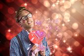 Geeky hipster covered in kisses against light design shimmering on red