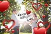 Loving young couple holding hands at park against happy valentines day