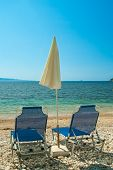 Sunbeds With Umbrellas On A Beautiful Beach With Clear Water