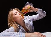 stock photo of forlorn  - Young beautiful woman in depression drinking alcohol - JPG