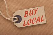 foto of local shop  - Advice to Buy Local printed on a brown paper price tag as a means of supporting local suppliers and producers - JPG