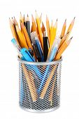 Group of pens and wooden pencils in metal vase isolated on white background