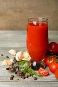 Glass of tasty tomato juice and fresh tomatoes on wooden table