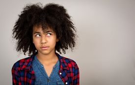 foto of wacky  - Young teenage girl with wacky afro hair looking up thinking and solving problems isolated against a grey background - JPG