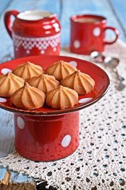picture of milkman  - small cone-shaped biscuits brown on the ceramic support of red on the background of mugs of cocoa and the milkman ** Note: Shallow depth of field - JPG