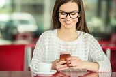 pic of pullovers  - Young smiling beautiful girl in glasses and white pullover sitting in urban cafe with a cup of coffee and reading messages on smart phone - JPG