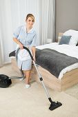 image of housekeeper  - Female Housekeeper Cleaning Rug With Vacuum Cleaner In Hotel Room - JPG