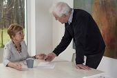 picture of divorce-papers  - Elderly man giving to his surprised wife divorce papers - JPG