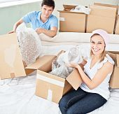 Merry Young Couple Unpacking Boxes With Glasses