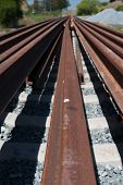 pic of railroad yard  - Multiple rails wait for installation on a train track