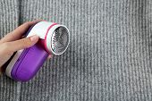 image of lint  - Female hands with Wool shaver on wool sweater background - JPG