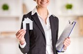 picture of model home  - Happy realtor woman is holding model of home and smiling - JPG