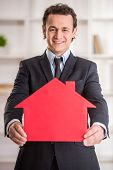 stock photo of possess  - Smiling realtor man is holding a model of home - JPG