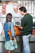 image of slaughterhouse  - Couple with digital tablet buying meat at butchery - JPG